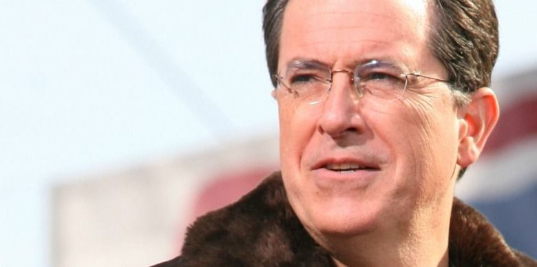 Stephen Colbert wearing glasses and smiling at the camera