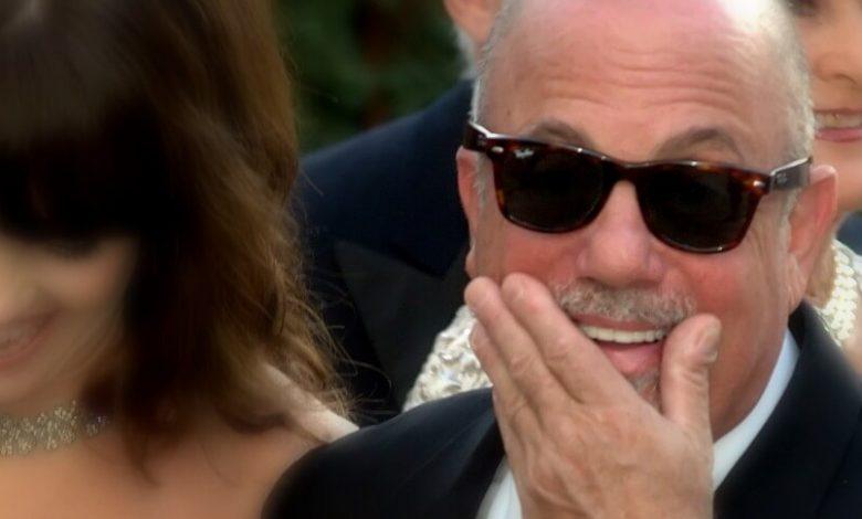 Billy Joel wearing sunglasses, with U2