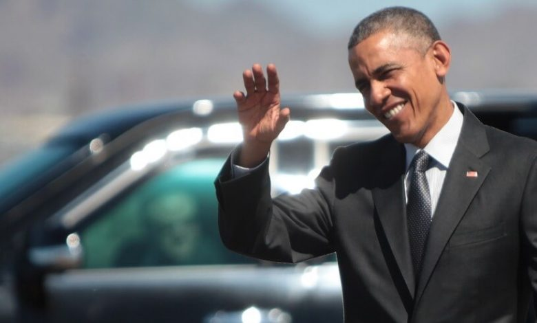 Barack Obama wearing a suit and tie talking on a cell phone